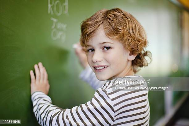 Boy writing on chalkboard in classroom