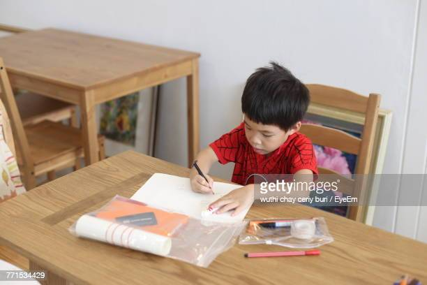 Boy Writing On Paper At Home