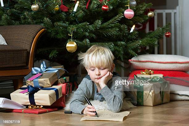 Boy writing under Christmas tree