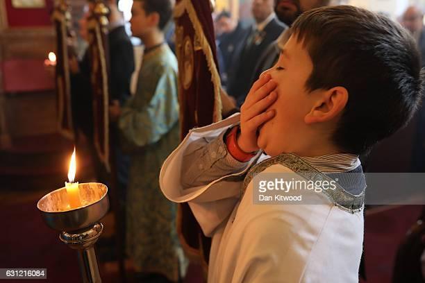 A boy yawns as Parishioners and clergy of the Greek Orthodox Church of St Michael the Archangel attend a service for Feast of the Epiphany on January...