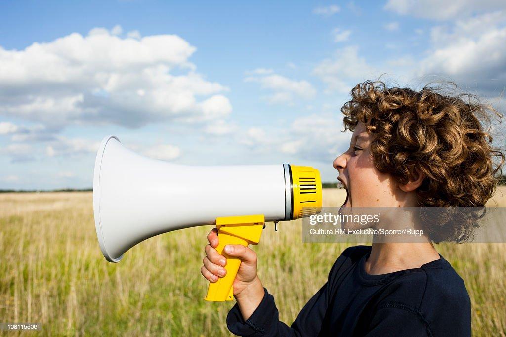 Boy yelling in megaphone : Stock Photo