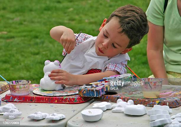 Boy/child doing outdoor painting / hand crafting