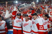 Boyd Devereaux Brett Hull and Pavel Datsyuk of the Detroit Red Wings raise the Stanley Cup after defeating the Carolina Hurricanes during game five...