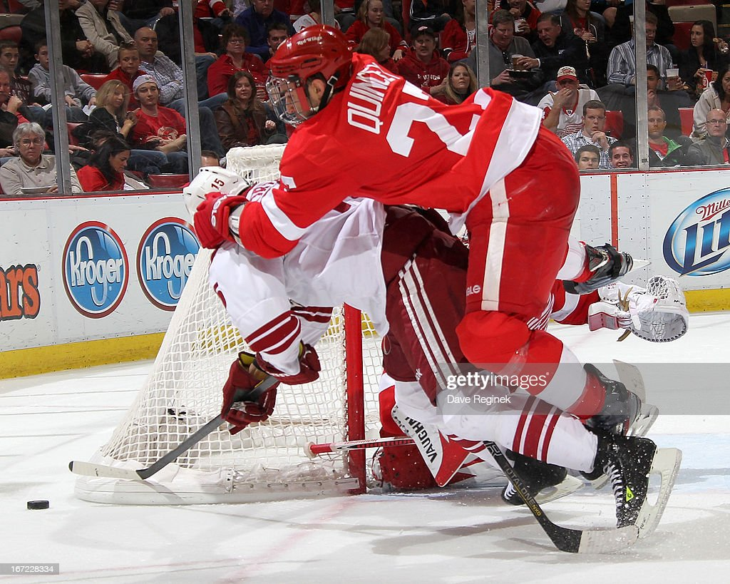 Boyd Gordan #15 of the Phoenix Coyotes gets jumped on from behind by Kyle Quincy #27 of the Detroit Red Wings as the puck goes behind the net during a NHL game at Joe Louis Arena on April 22, 2013 in Detroit, Michigan.