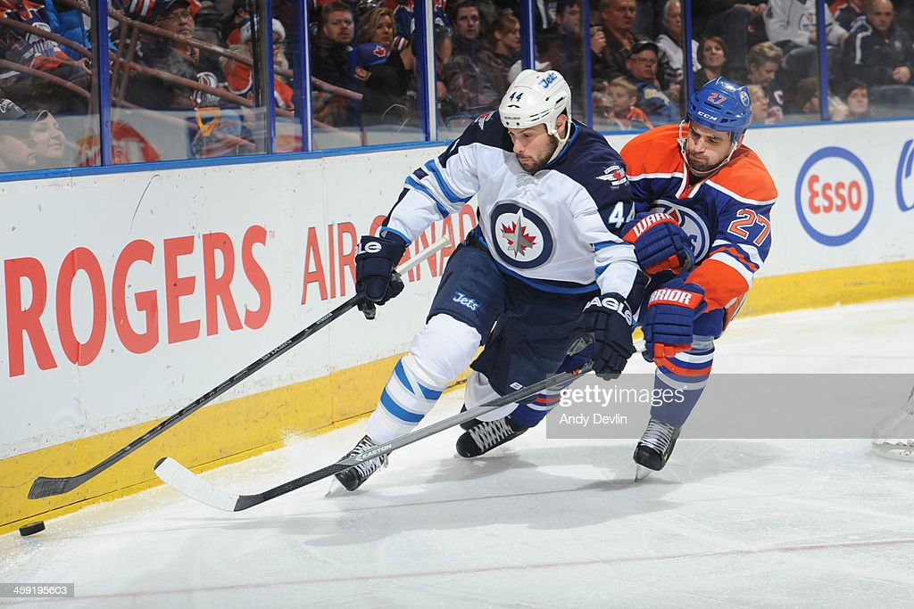 <a gi-track='captionPersonalityLinkClicked' href=/galleries/search?phrase=Boyd+Gordon&family=editorial&specificpeople=209395 ng-click='$event.stopPropagation()'>Boyd Gordon</a> #27 of the Edmonton Oilers battles for the puck against <a gi-track='captionPersonalityLinkClicked' href=/galleries/search?phrase=Zach+Bogosian&family=editorial&specificpeople=4195061 ng-click='$event.stopPropagation()'>Zach Bogosian</a> #44 of the Winnipeg Jets on December 23, 2013 at Rexall Place in Edmonton, Alberta, Canada.