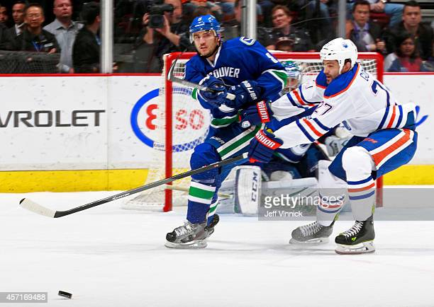 Boyd Gordon of the Edmonton Oilers checks Christopher Tanev of the Vancouver Canucks as he passes the puck up ice during their NHL game at Rogers...