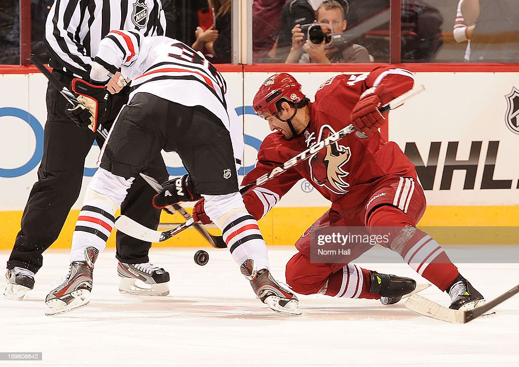 Boyd Gordon #15 of the Phoenix Coyotes wins a faceoff against Dave Bolland #36 of the Chicago Blackhawks at Jobing.com Arena on January 20, 2013 in Glendale, Arizona.
