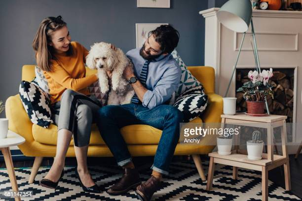 Boyfriend and girlfriend playing with dog on the sofa