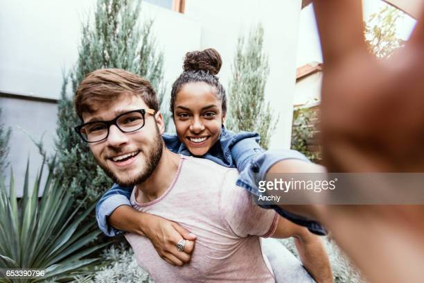Boyfriend and girlfriend taking selfie, piggy back ride