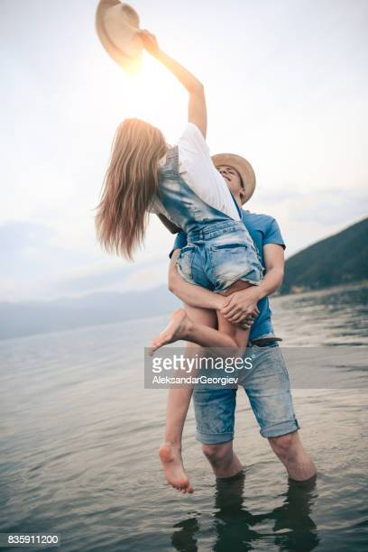 Boyfriend Holding his Girlfriend in his Arms with Raised Hat