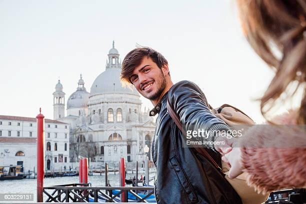 boyfriend pulling girlfriend towards Venice lagoon