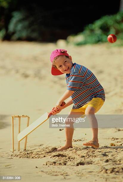 Boy(4-6)in beachwear & cap playing cricket on beach, ball in air