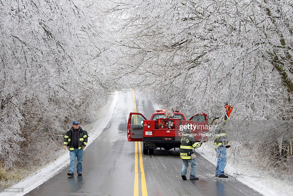 Boyle County Fire Dept firefighters Lt Charles Johnson Clint Owens Darin Horton and Darin Horton remove low hanging limbs during a morning winter...
