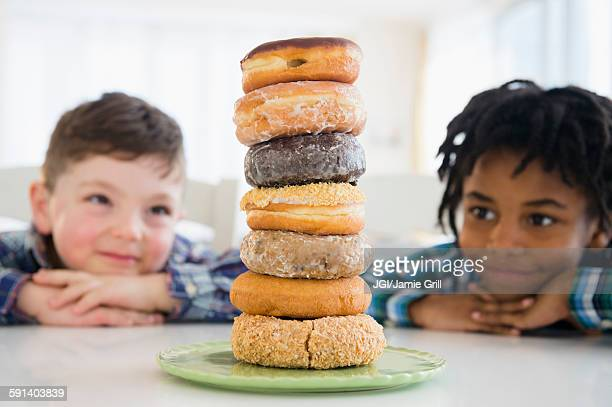 Boys admiring stack of donuts on counter