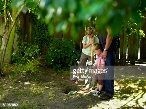 boys and dad in yard burying pet