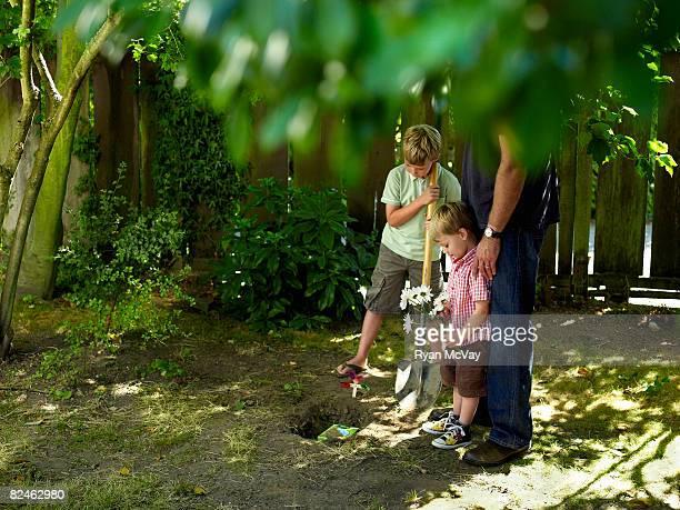 T boys and dad in yard burying pet