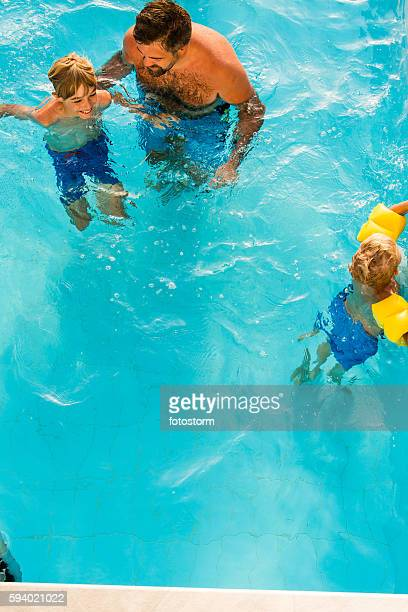 Boys and father swimming in pool