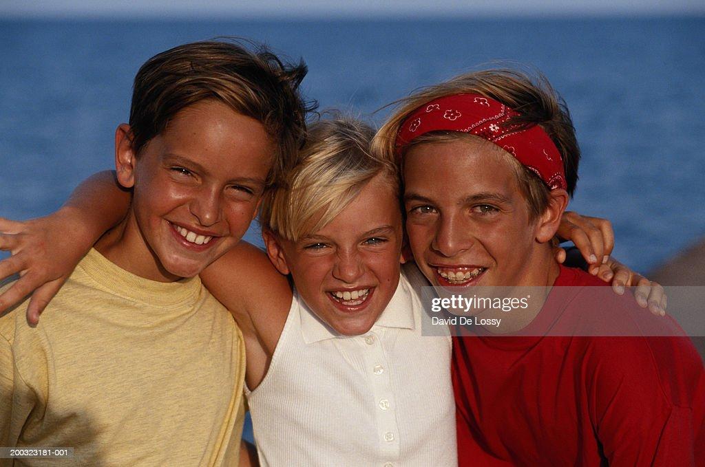 Boys (8-12) and girl (4-7) smiling, arm around, portrait : Stock Photo