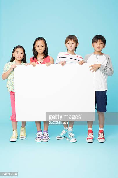 Boys and girls holding white board, studio shot