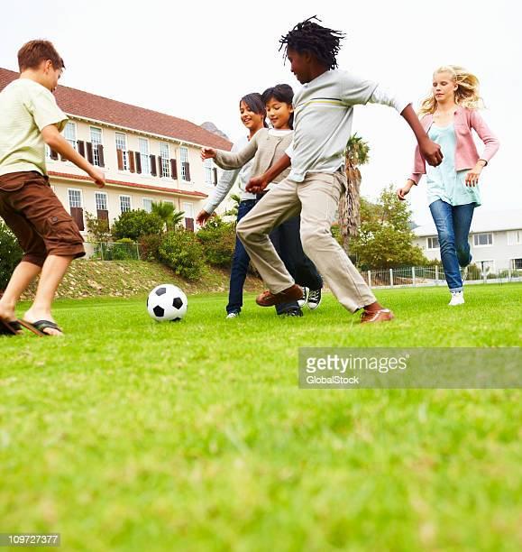 Jungen und Mädchen spielen Fußball im park