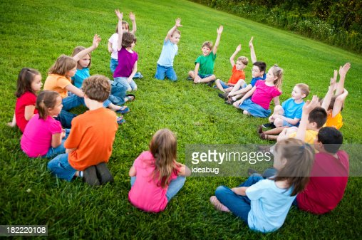Boys and Girls Sitting in a Circle Raising Hands