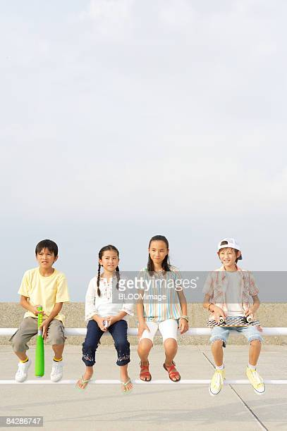 Boys and girls sitting on guardrail