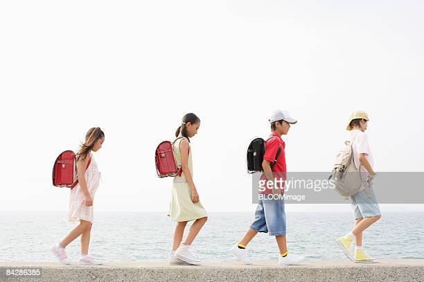 Boys and girls walking on floodwall