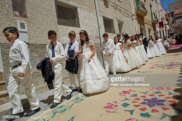 Boys and girls wearing white dress from the communion take part in a procession as they walk over sawdust carpets during the Corpus Christi feast on...