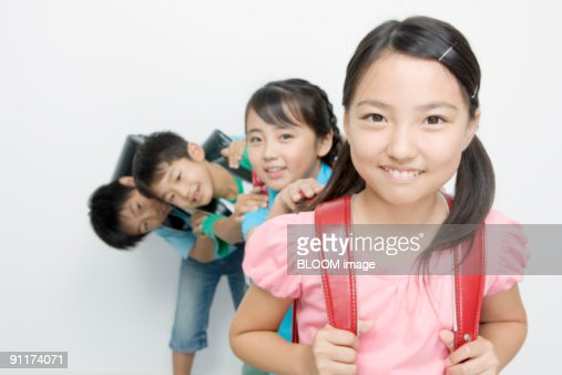 Boys and girls with school satchels : Stock Photo