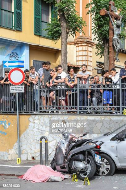 Boys and locals observe the two bodies of the two men a 45yearold and 22yearold killed while on board scooter both of whom were called Carlo Nappello...