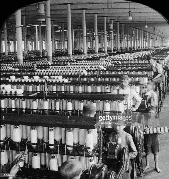Boys and men work within huge rows of spinning machines in the spinning room of the Olympian Cotton Mills Columbia South Carolina