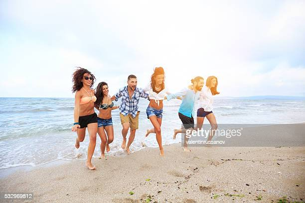 Boys ans girls running on the beach-hand to hand