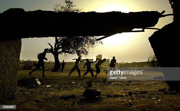 Boys are framed by a broken bench as they play soccer on a makeshift field February 19 2004 in Baghdad Iraq US administrator Paul Bremer said today...