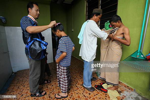 Boys are prepared by their fathers before a mass circumcision ceremony in Kajang outside Kuala Lumpur on November 20 2011 About 30 boys aged between...