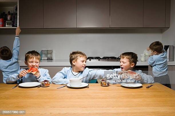 Boys (8-10) arguing at the breakfast table