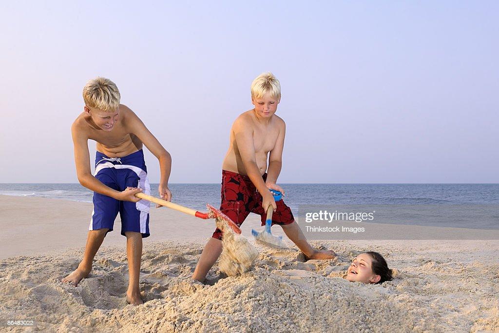 Boys burying girl in sand