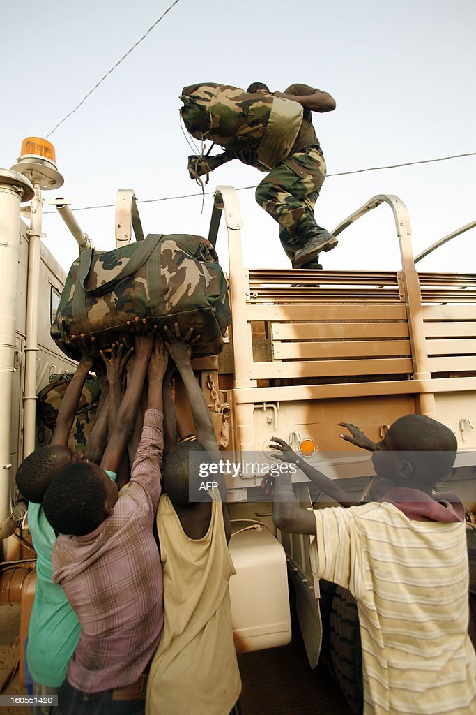 Boys carry a bag as a senegalese soldier standing on a truck holds a bag, at the Captain Moussa Dioum military camp of Bargny, near Dakar, on February 2, 2013, before leaving for Mali as part of the second contingent of Senegalese troops to back Malian forces. French President Francois Hollande received a rapturous welcome in Mali on Saturday as he promised that France would stay as long as necessary to continue the fight against Islamist rebels in the country's north.As troops worked to secure Kidal, the last bastion of radicals who occupied the vast desert north for 10 months before the French army's surprise intervention, Hollande told Malians it was time for Africans to take the lead but that France would not abandon them. AFP PHOTO/Mamadou Toure BEHAN
