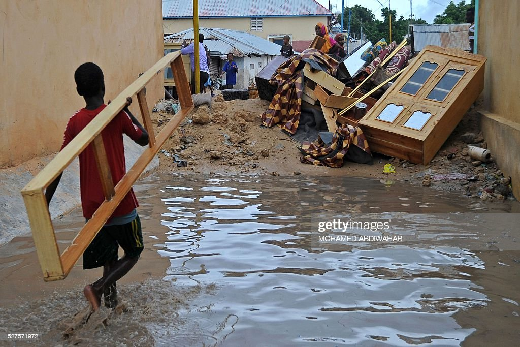 Boys carry their family's belongings to higher ground after their home was inundated by floods in Mogadishu on May 3, 2016 following heavy rainfall overnight. / AFP / MOHAMED