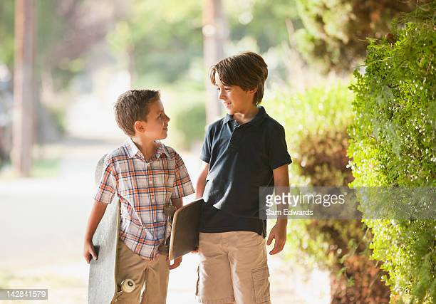 Boys carrying skateboards on suburban street