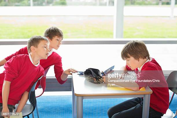 Boys cheating from students work in classroom
