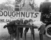 Boys Chow Down on a Table in a Donut Eating Contest for the Salvation Army
