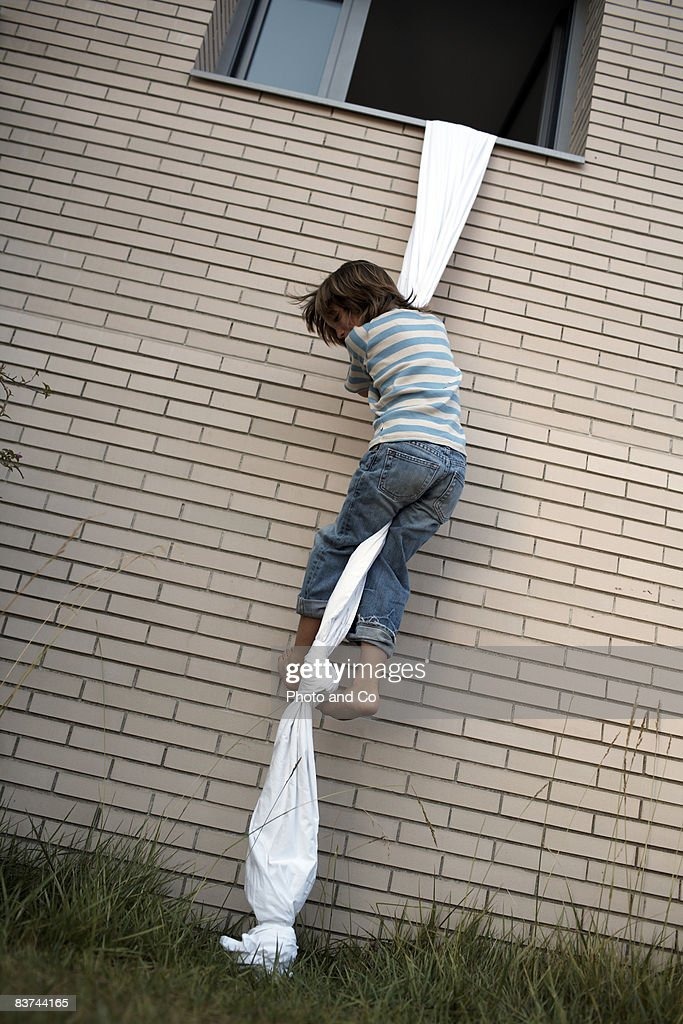 boys climbs out of window using sheet rope : Stock Photo