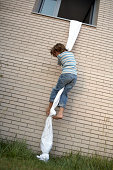 boys climbs out of window using sheet rope