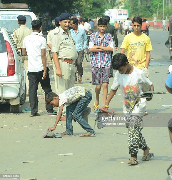 Boys collects the footwear of victims of stampede occurred during the Dussehra celebration at Gandhi Maidan on Friday night on October 4 2014 in...
