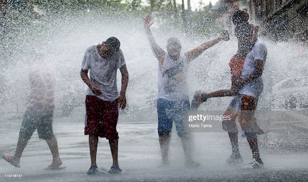 Boys cool off in water sprayed from a fire hydrant on June 9, 2011 in the Bronx borough of New York City. An early summer heat wave has hit the city with temperatures forecast to hit in the high nineties this afternoon.