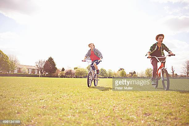 Boys cycling on playing field