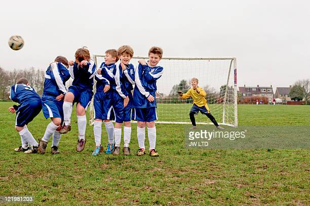 Boys defending free kick during football game