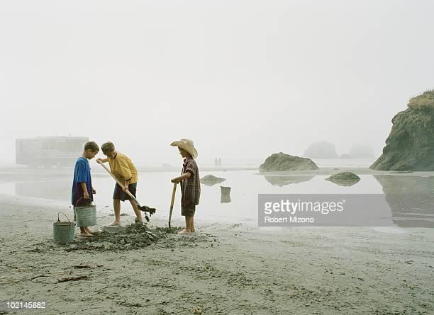 Boys digging hole on beach
