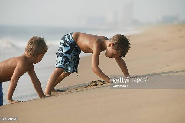 Boys digging in beach sand