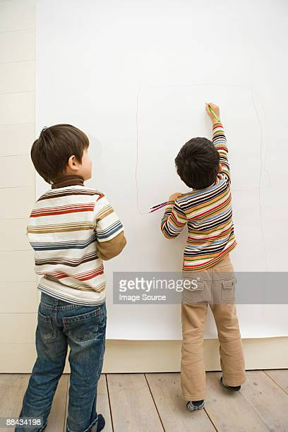 Boys drawing on a wall